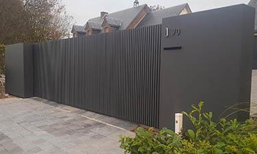 Moderne schuifpoort met verticale kokers en vaste panelen - Faimes