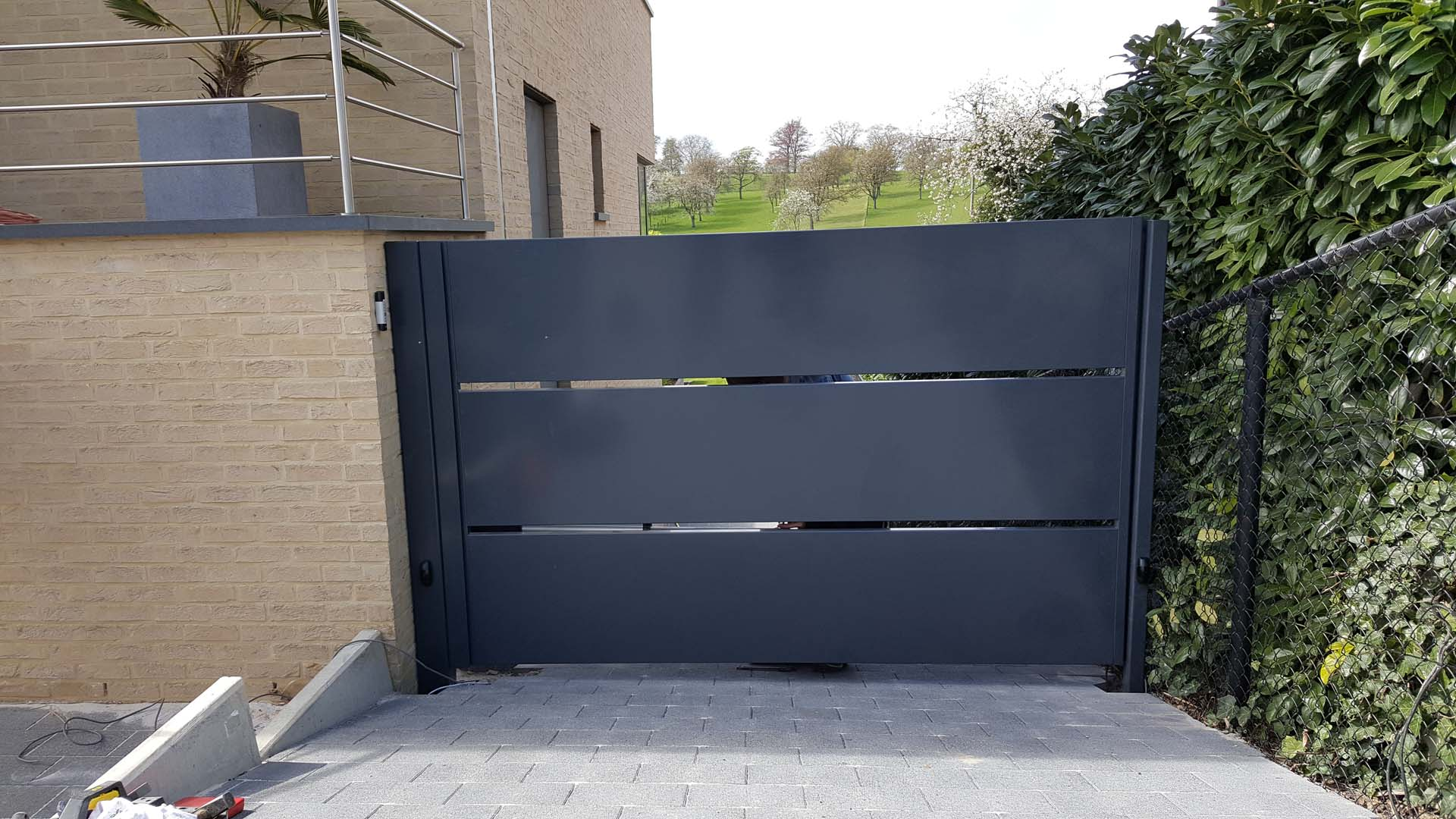 Moderne aluminium vleugelpoort met horizontale panelen te Borgloon, Limburg