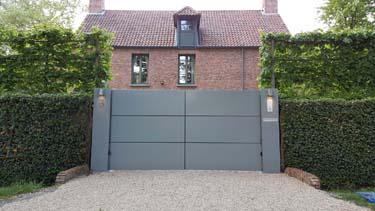 Moderne aluminium vleugelpoort met twee brede zuilen te Antwerpen